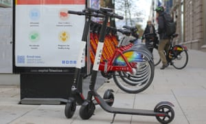 Bird dockless electric scooters next to a bike-sharing docking station in Washington DC
