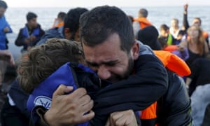 A Syrian refugee embraces his son after their overcrowded raft landed at a rocky beach in the Greek island of Lesbos on 19 November 2015.