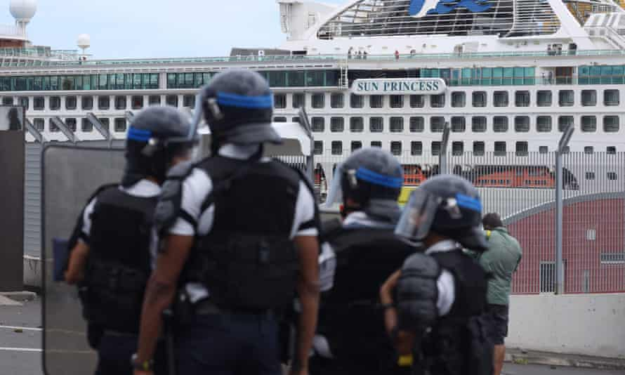 Police on Réunion Island face demonstrators as people protest against the arrival of passengers of the Sun Princess cruise ship without having their temperature checked.