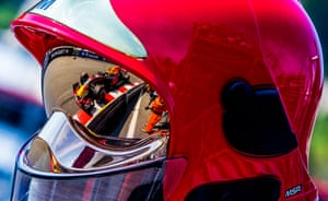 Dutch Formula One driver Max Verstappen of Red Bull Racing is reflected in a helmet of Monaco fireman during the first practice session at Monte Carlo circuit, Monaco