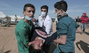 Palestinian paramedics carry a protester injured during clashes with Israeli forces at the Israel-Gaza border, 2 April 2018.