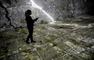A visitor uses a tablet computer as she walks over an interactive map of Berlin marking the course of the Berlin Wall and sites relating to the Stasi