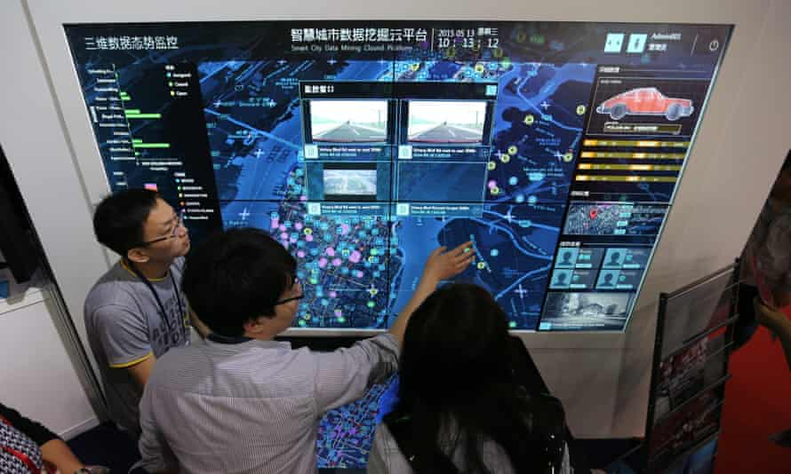 Visitors look at a screen displaying a smart city system at the 18th China Beijing International High-Tech Expo in Beijing, China, 13 May 2015.