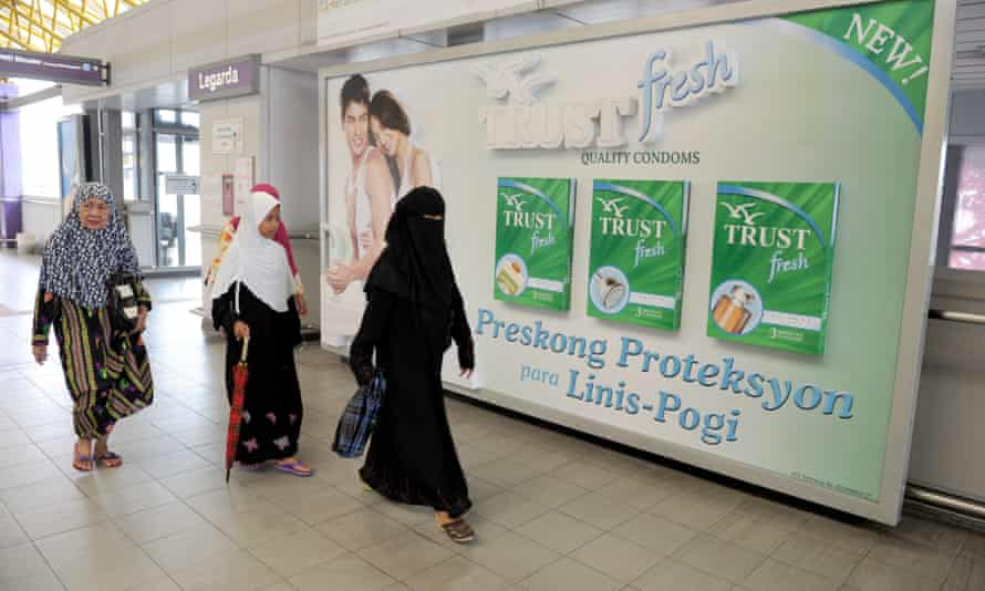 A group of Muslim women walk in front of an advertisement for condoms in Manila
