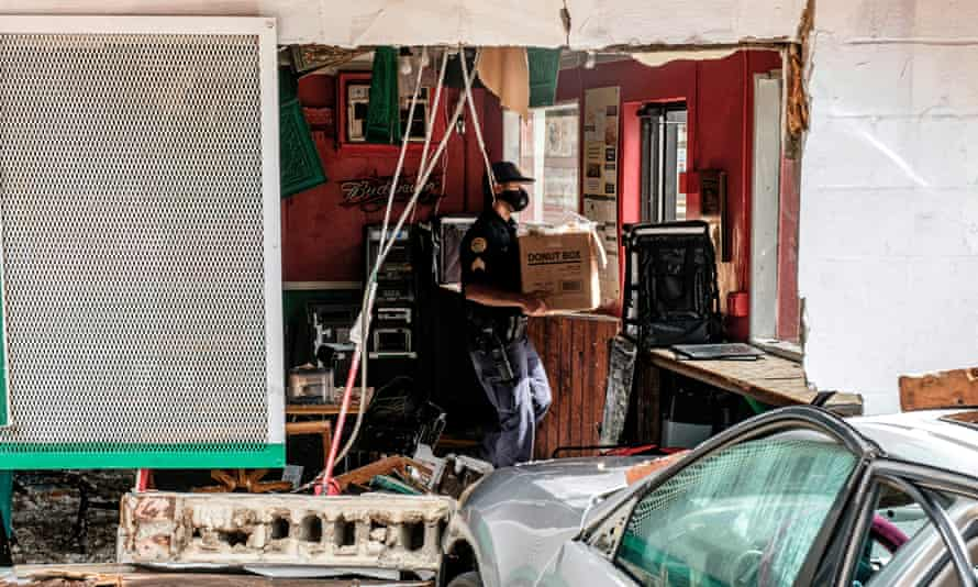A member of the New Orleans police department carries a box of food out of a damaged restaurant.