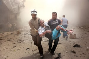 Search and rescue team members carry a man after Syrian regime airstrikes targeted the Meshed neighbourhood of Aleppo
