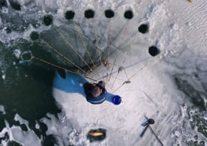Beijing, China: a fishing enthusiast steers rods through holes in thin ice to catch fish