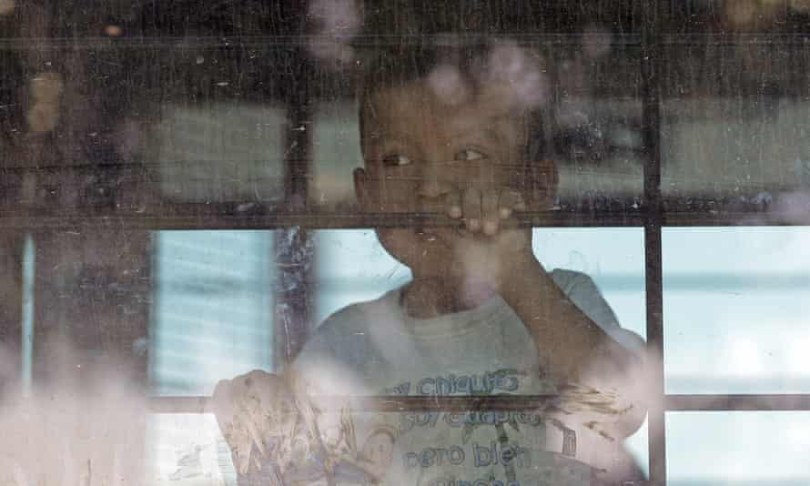 An immigrant child looks out from a US border patrol bus in McAllen, Texas, on 23 June 2018.