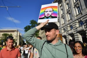A protestor with a poster of Vladimir Putin in rainbow colours at a demonstration in Budapest