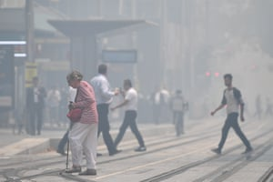 Pedestrians cross George Street as smoke haze blankets Sydney