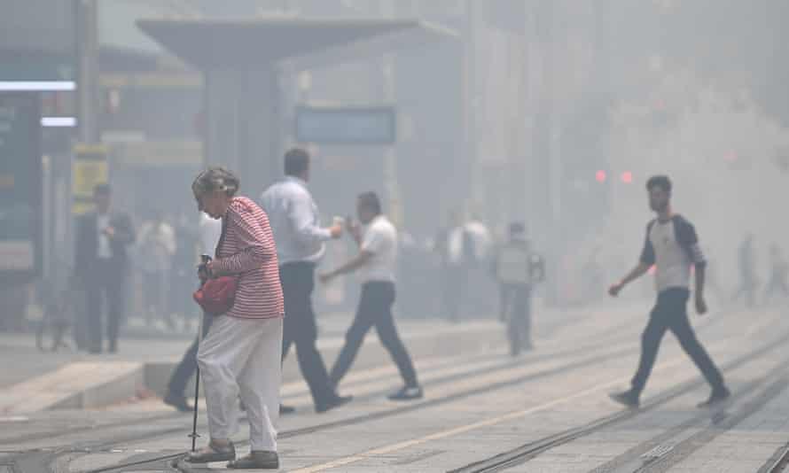 pedestrians walk in smoke haze in the city