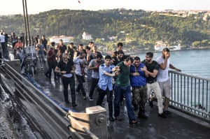People apprehend a Turkish soldier, third right in blue, who participated in the attempted coup in Istanbul