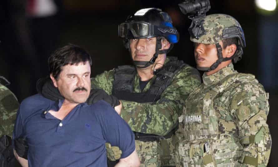 Joaquín 'El Chapo' Guzmán made to face the press as he is escorted by Mexican soldiers in January.