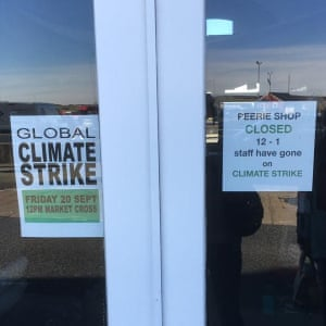 signs in a shop window with one saying the shop is closed between 12 and 1 because staff have gone on climate strike