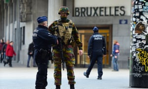 A Belgian soldier speaks to a police officer outside Brussels Central Station as people are allowed in small groups of ten to reach the station in order to take their commuter train following attacks in Brussels.