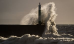 Waves batter the lighthouse and harbour wall in Aberystwyth, Wales