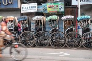 Rickshaws are parked up on a roadside in Kolkata