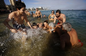 Swimmers try to catch a cross after it was thrown by an Orthodox priest into the water at Famagusta beach, Cyprus