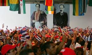 Members of the Cuban delegation wave flags beneath portraits of the South American libertor Simón Bolívar and the Cuban national hero José Martí at the World Social Forum in Caracas, Venezuela, in 2006.