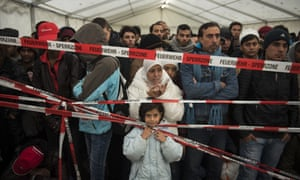 FILE- Newly arrived immigrants are kept behind a cordon as the wait to be let into a pre-register site to allow them to be bussed to a newly opened asylum seeker registration centre at the Office of Health and Social Affairs LAGESO, October 15, 2015 in Berlin.