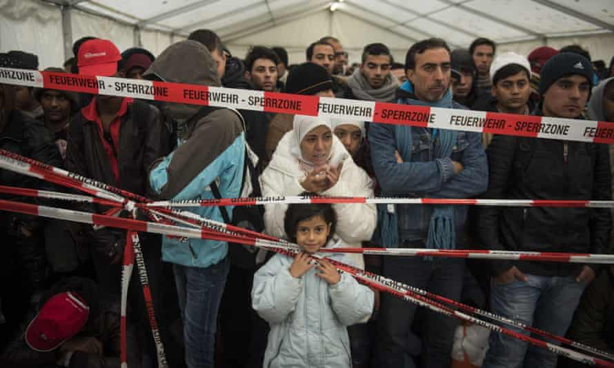Migrants wait to be transported to a registration centre in Berlin in 2015