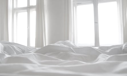 White bed linen with two windows in the background