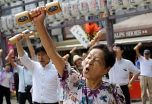 Elderly people work out with wooden dumb-bells in the grounds of a temple in Tokyo on September 21, 2015, to celebrate Japan's Respect for the Aged Day. The estimated number of people aged 80 or older in Japan topped 10 million for the first time, the government announced.