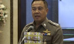 National police chief Somyot Poompanmoung holds a cash reward at a press conference in Bangkok.