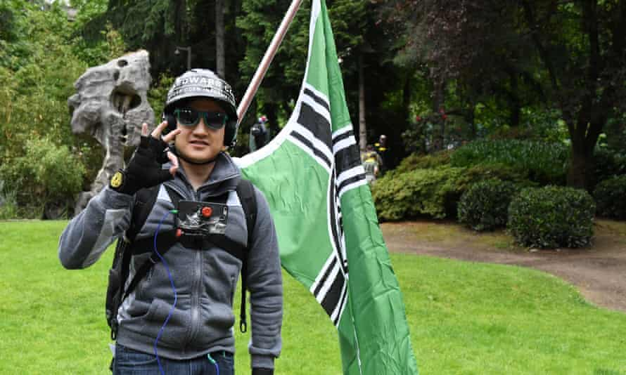 An activist makes a far-right hand signal.