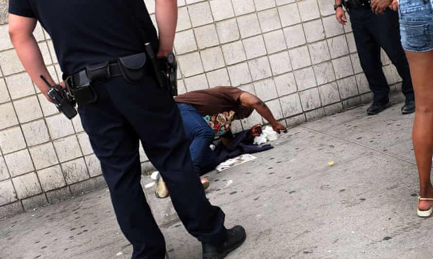 Police stand over a man passed out due to 'synthetic marijuana' in East Harlem in September.