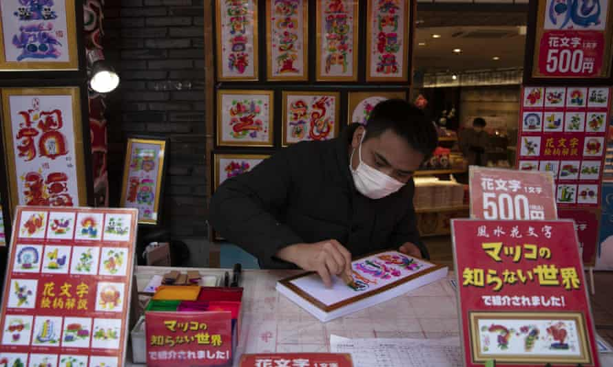 A vendor wears a mask  in Yokohama's Chinatown, near Tokyo where the Olympics are due to start in July.