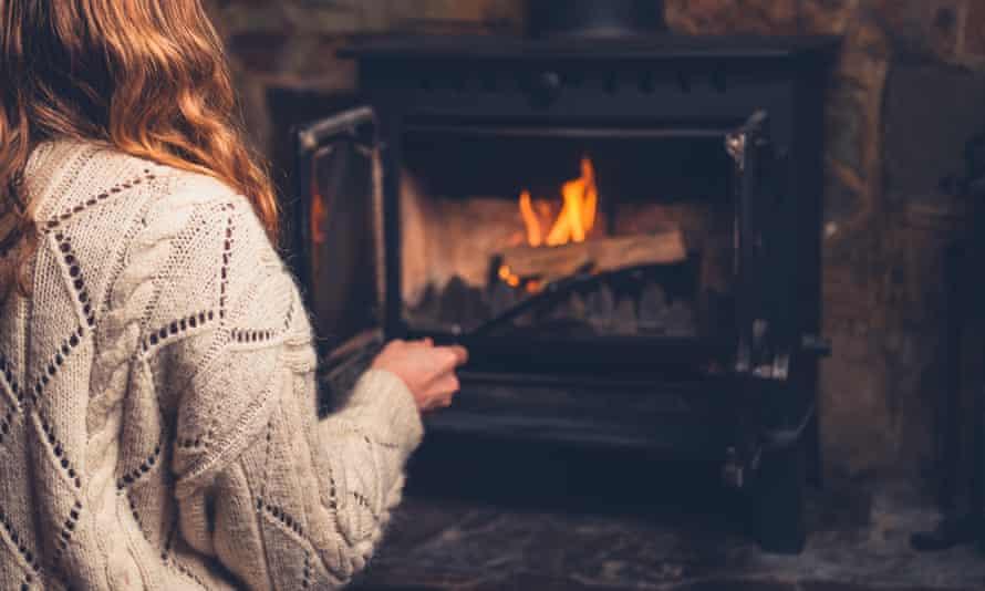 Mlada ženska v volnenem skakalcu kadi ogenj v hlodu