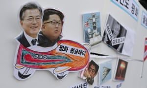 Pictures of South Korean President Moon Jae-in and North Korean leader Kim Jong Un seen on a sign during a rally. Moon's popularity is falling due to overtures to the North.