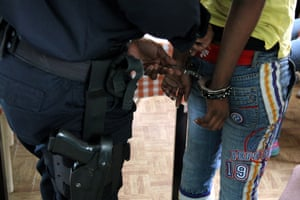 Detroit police officer placing handcuffs on a suspect.