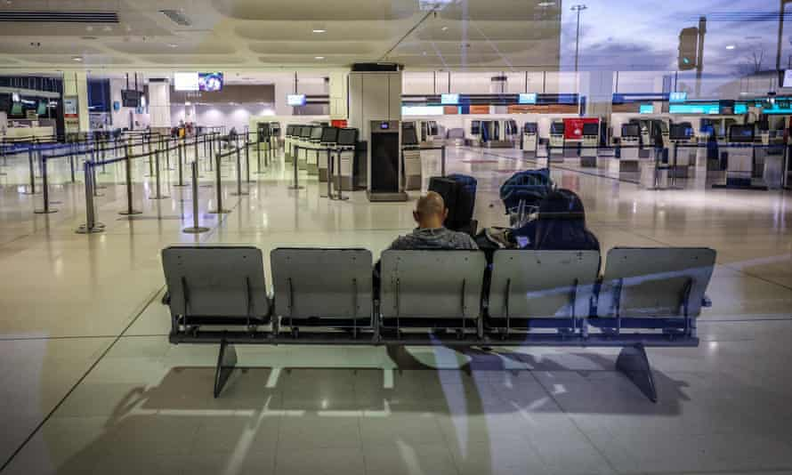 Two passengers waiting to check in for their flight in the otherwise-deserted departures area of the Sydney international airport in Sydney