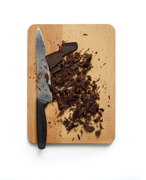 Chopping board with large knife and chocolate shards