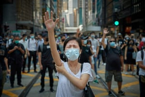 Reportage: Hong Kong Pro-Democracy Protests by Kiran Ridley. A protester holds her hand in the air to represent 'five demands' as people gather in central Hong Kong to demonstrate against the introduction of the government's anti-mask law on 4 October 2019.