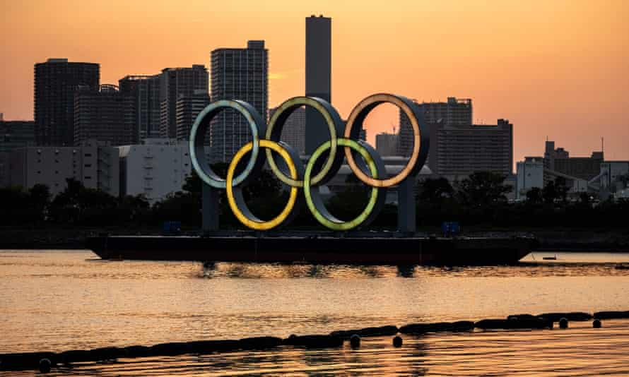 skyline of tokyo with olympic rings against an orange sky
