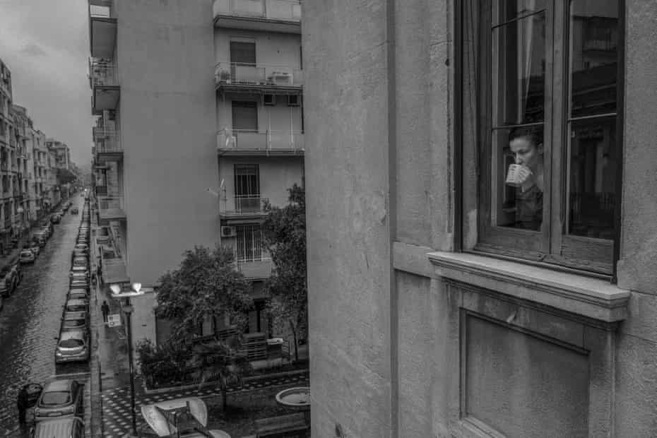 Marta at the window while drinking a herbal tea. In the background, some people queue in the street waiting to enter the supermarket below the apartment.