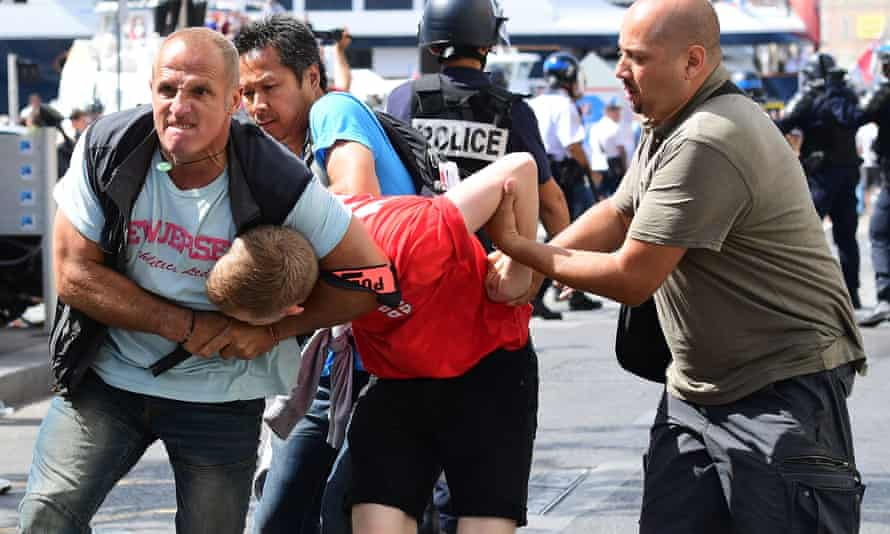 An England fan is detained by police following clashes between England fans and police in Marseille, France