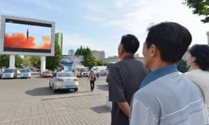North Koreans watch an intermediate-range ballistic missile launch in Pyongyang. Japan now fears a nuclear-armed missile will be launched over its territory.