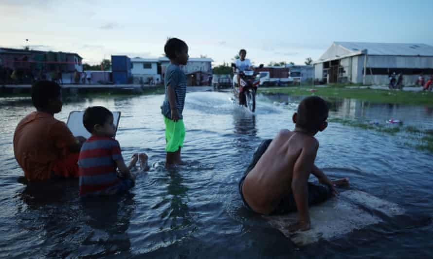 Boys play in flood waters on Tuval, an island that is extremely vulnerable to climate change