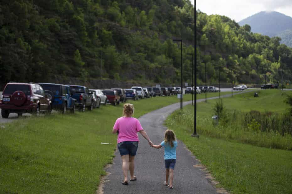A mother and daughter walk past a line of miners' cars down Highway 421 in Harlan, Kentucky. Many questions about Blackjewel's operations have not been answered.