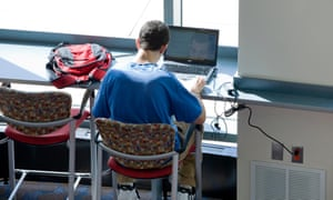 A file photo of a university student working on his laptop computer