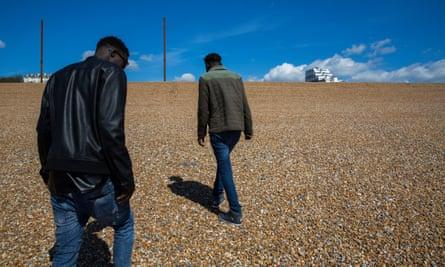 Young Sudanese unaccompanied asylum seekers walk on the beach of the Kent coast