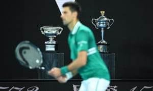 The Norman Brooks Challenge Cup and the Daphne Akhurst Memorial Cup are seen behind Djokovic as he closes in on victory.