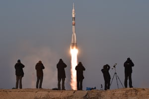 Photographers take pictures as Russia's Soyuz TMA-19M spacecraft carrying the International Space Station crew blasts off from Baikonur cosmodrome in Kazakhstan