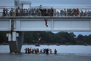 An immigrant jumps off a bridge to enter Mexico from the border with Guatemala as part of the immigrant caravan on October 20, 2018 in Ciudad Hidalgo, Mexico.