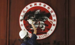 A protester defaces the Hong Kong emblem after breaking into the Legislative Council building in Hong Kong on 1 July
