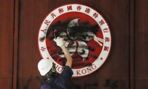 A protester defaces the Hong Kong emblem